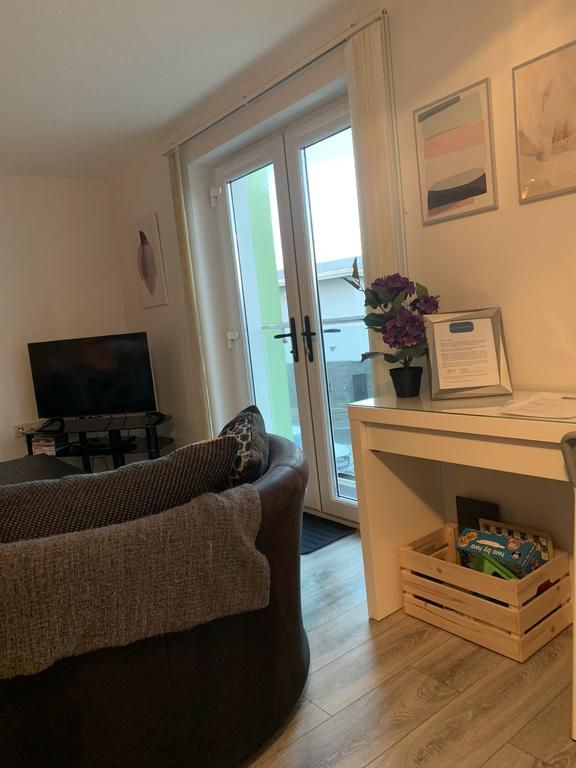 Peninsula Apartment Portrush - living room with a flat TV