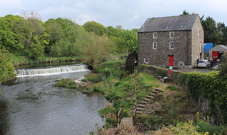 An image of cURRYS mill with water wheel on the River Bush in Bushmills