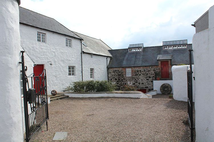 am image of Palmers Mill in bushmills. The mill sits on the River Bush and has a wheel attached