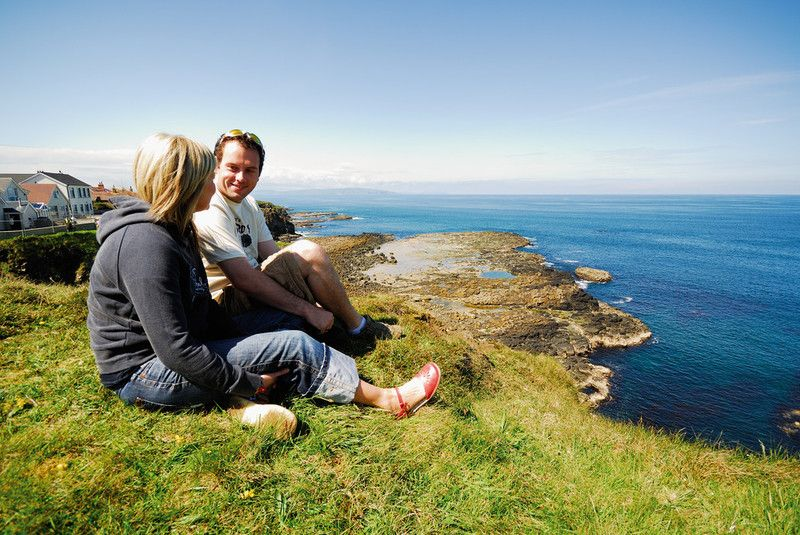 Cliffs-overlooking-Portrush with couple stopping after a walk along the coastal path