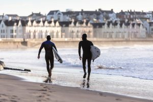 Things to do in Portrush two surfers walking along west strand beach portrush